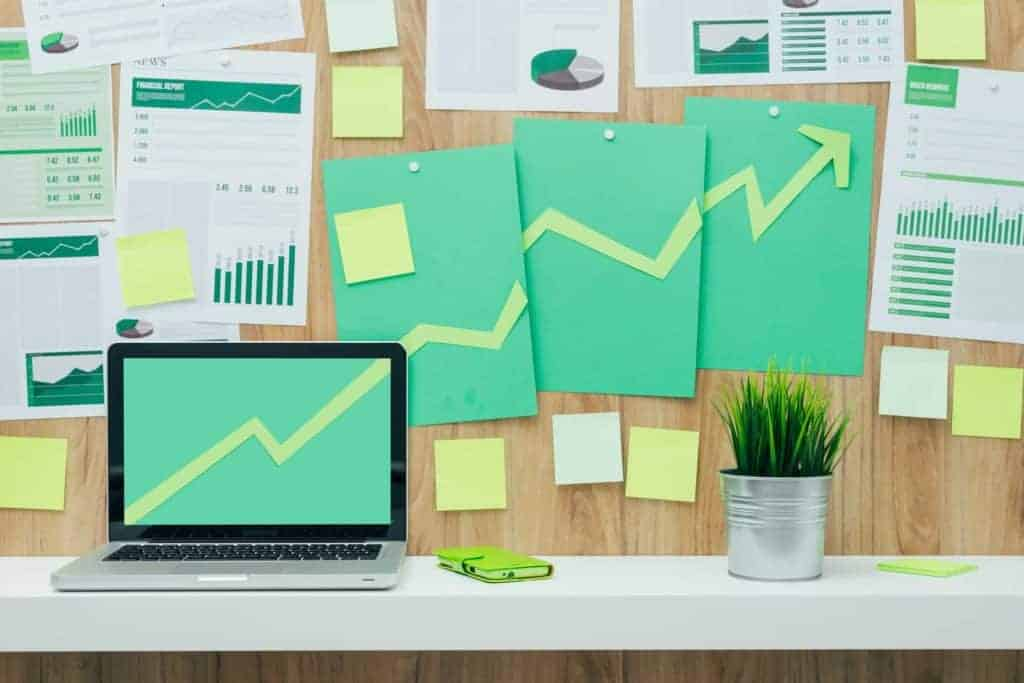 Successful financial chart with arrow pointing up composed of green paper cuts hanging on a wall and laptop, eco business and financial success concept