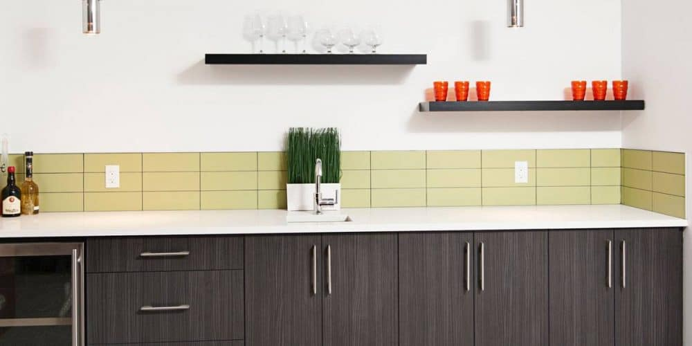small minimalist kitchen sink with a few lime coloured tiles surrounding the bottom edge of the walls