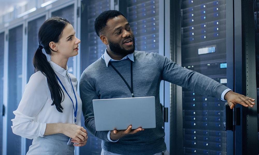 IT-Techniker mit einem Laptop-Computer gibt einer jungen Praktikantin eine Führung. Sie unterhalten sich im Rechenzentrum, während sie neben den Serverschränken gehen. Sie führen Wartungsarbeiten durch.