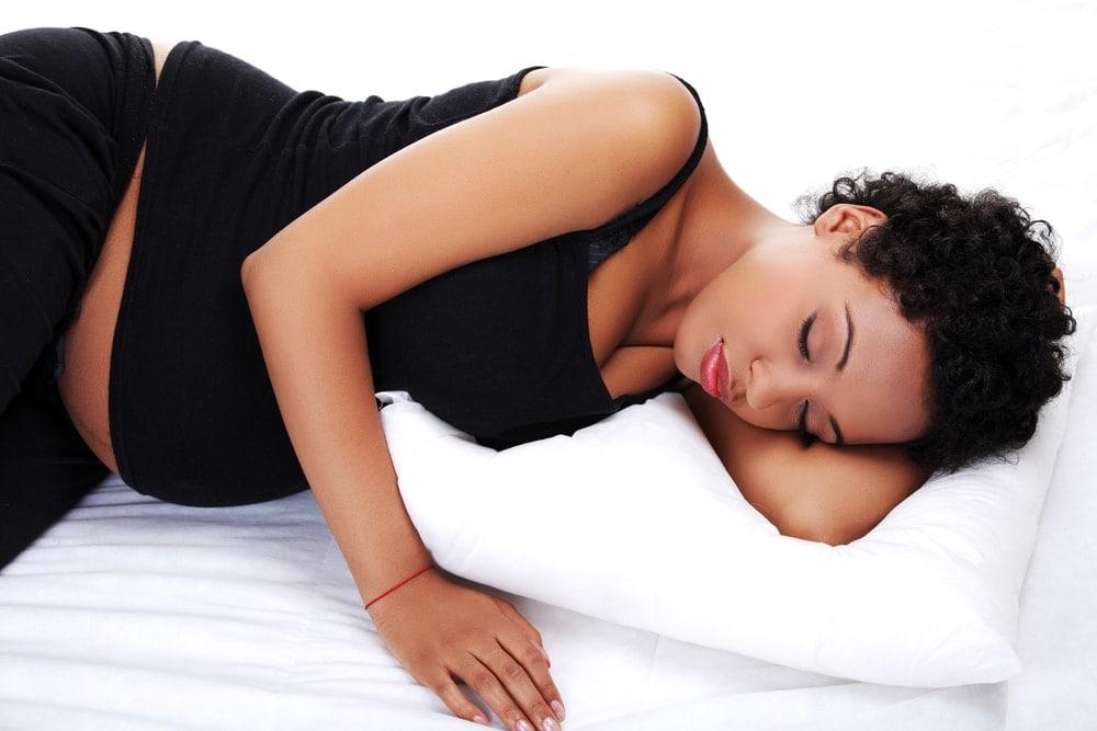 Mujer embarazada tratando de encontrar la mejor posición para dormir