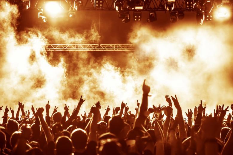 толпа на концерте с поднятыми руками и дым фото
