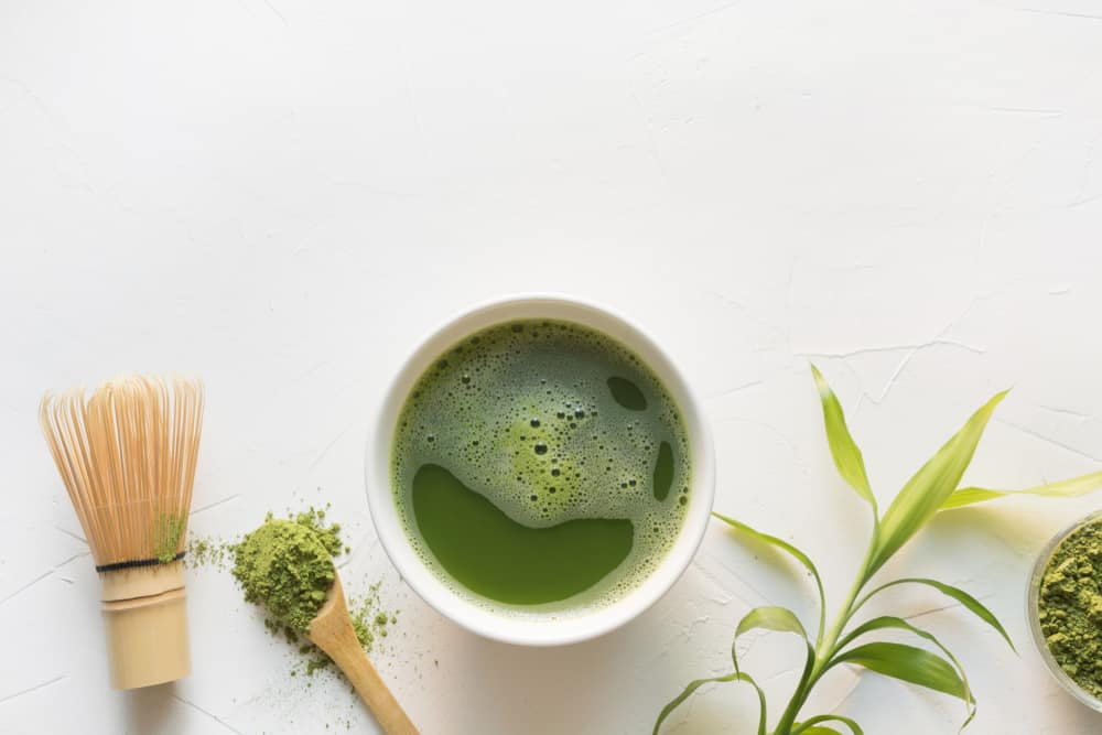 Traditional green matcha tea in bowl and bamboo whisk on white concrete table