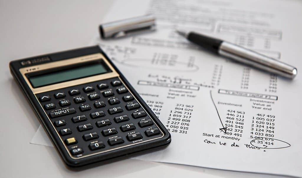 Een rekenmachine, pen en papier met berekeningen erop