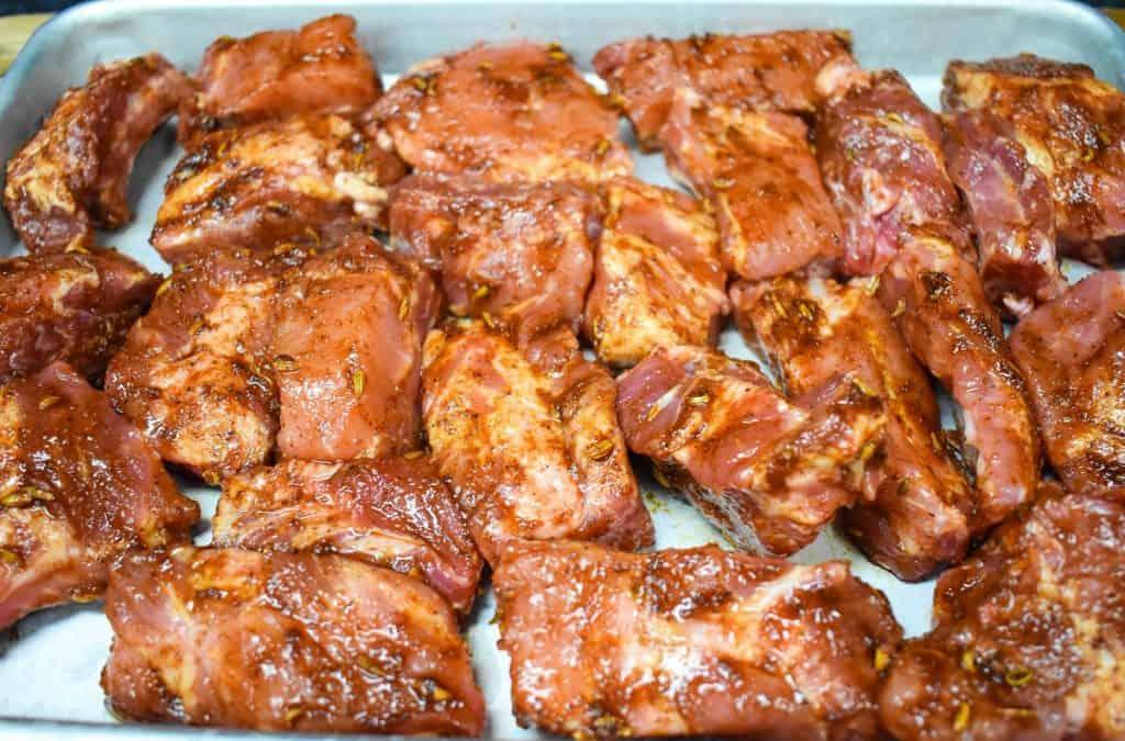Pork riblets with a seasoning rub, arranged on a metal baking sheet.