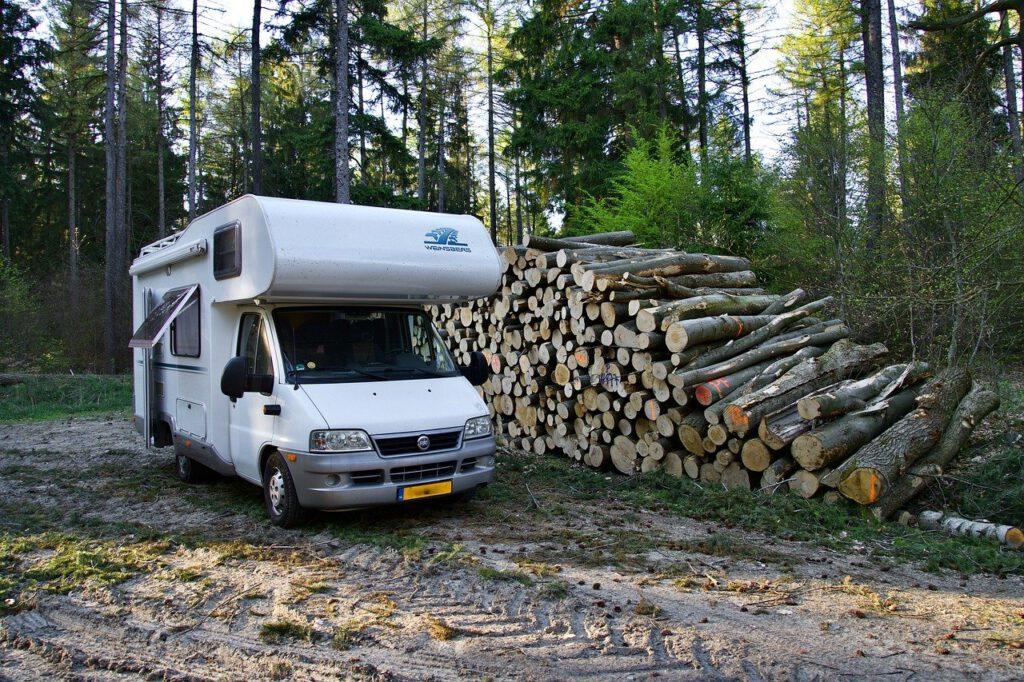 Camper naast houtstapel wildkamperen Camper Deluxe