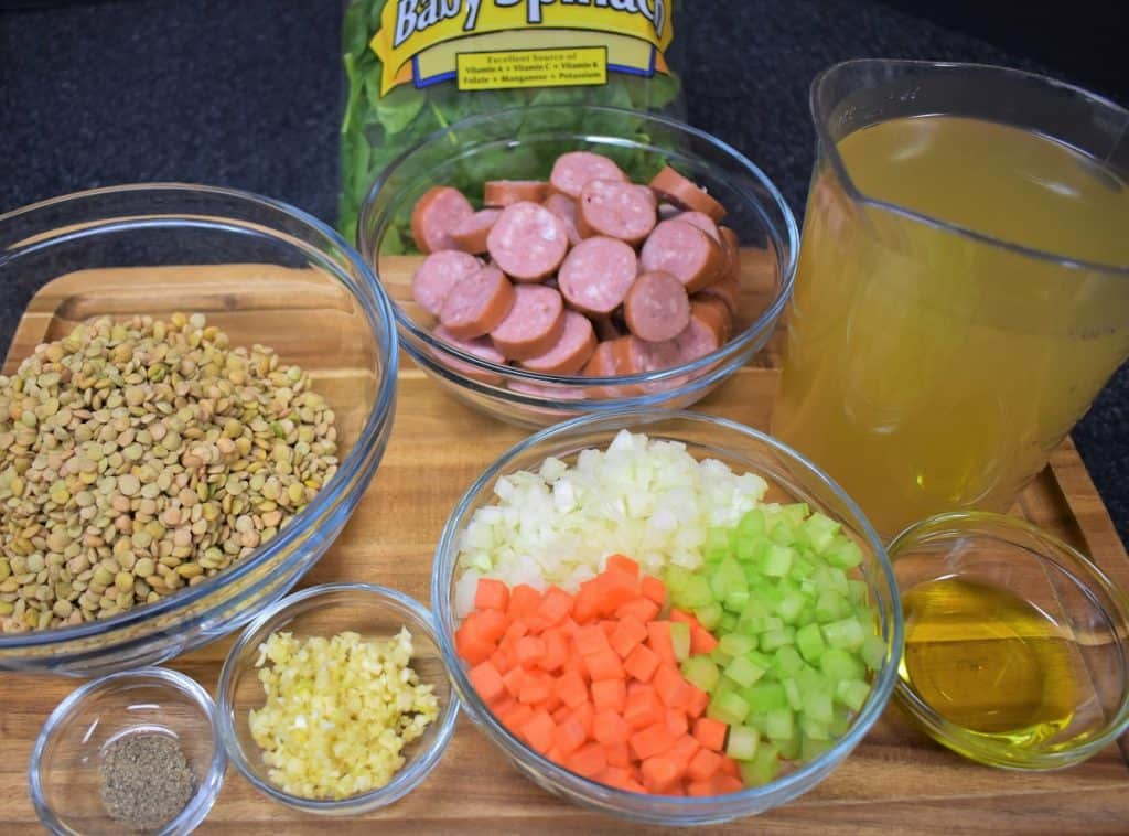 The ingredients for the lentil sausage soup displayed on a wood cutting board.