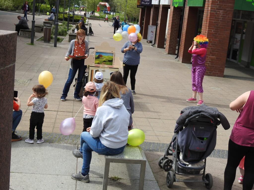 Grupa dorosłych i dzieci zwrócona w stronę 3 osób, z których jedna stoi obok drewnianej skrzynki z kolorowymi obrazkami, czyta. Obok osoba w balonami, a z jej boku postać w stroju clowna.