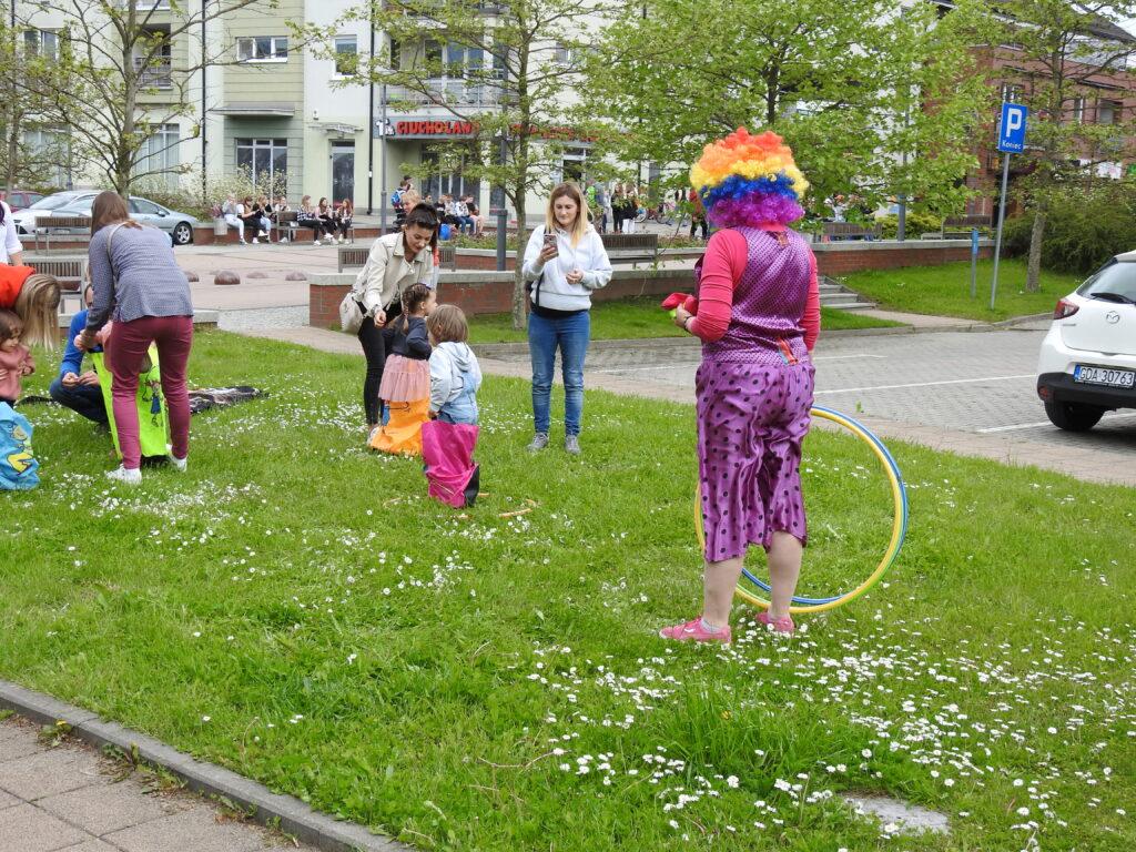 Postać w stroju clowna na świeżym powietrzu hulahoopem, dziecko skaczące w pomarańczowym worku..