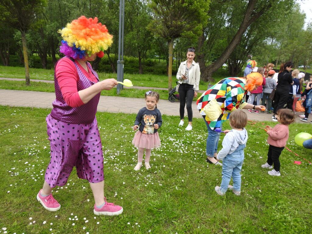 Postać w kolorowym stroju i peruce niesie na łyżce jajko. Przed nią małe dzieci.