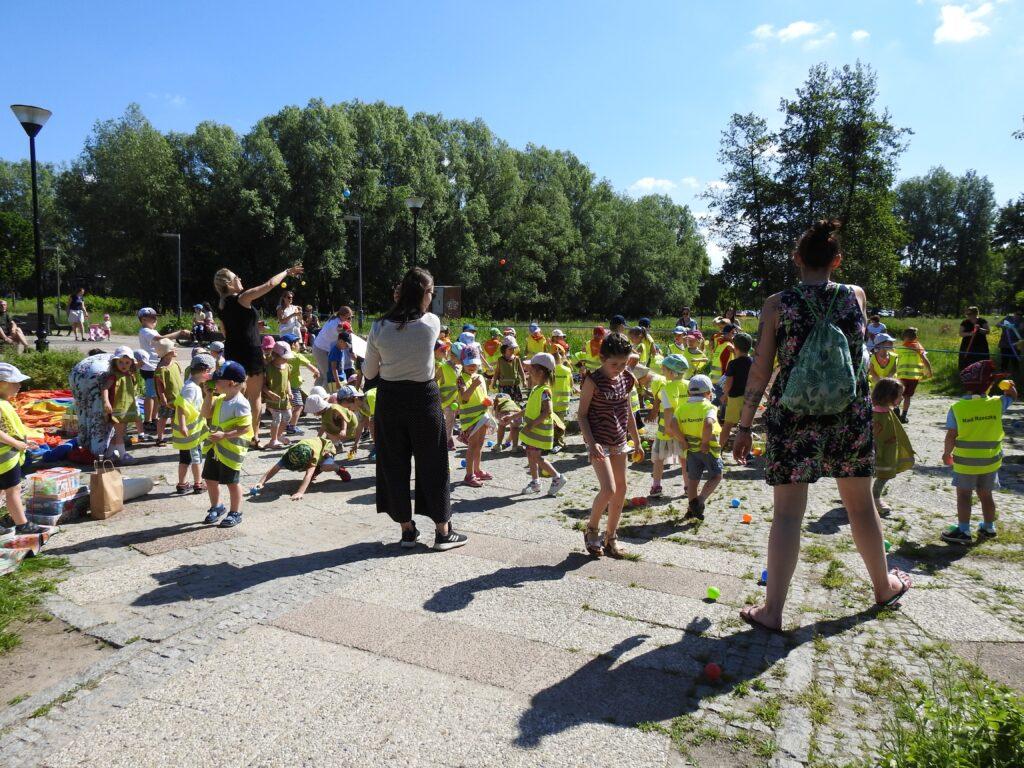 Duża grupa dzieci oraz kilkoro dorosłych na świeżym powietrzu. Niektózy trzymają line , pod nią leżą kolorowe piłki.