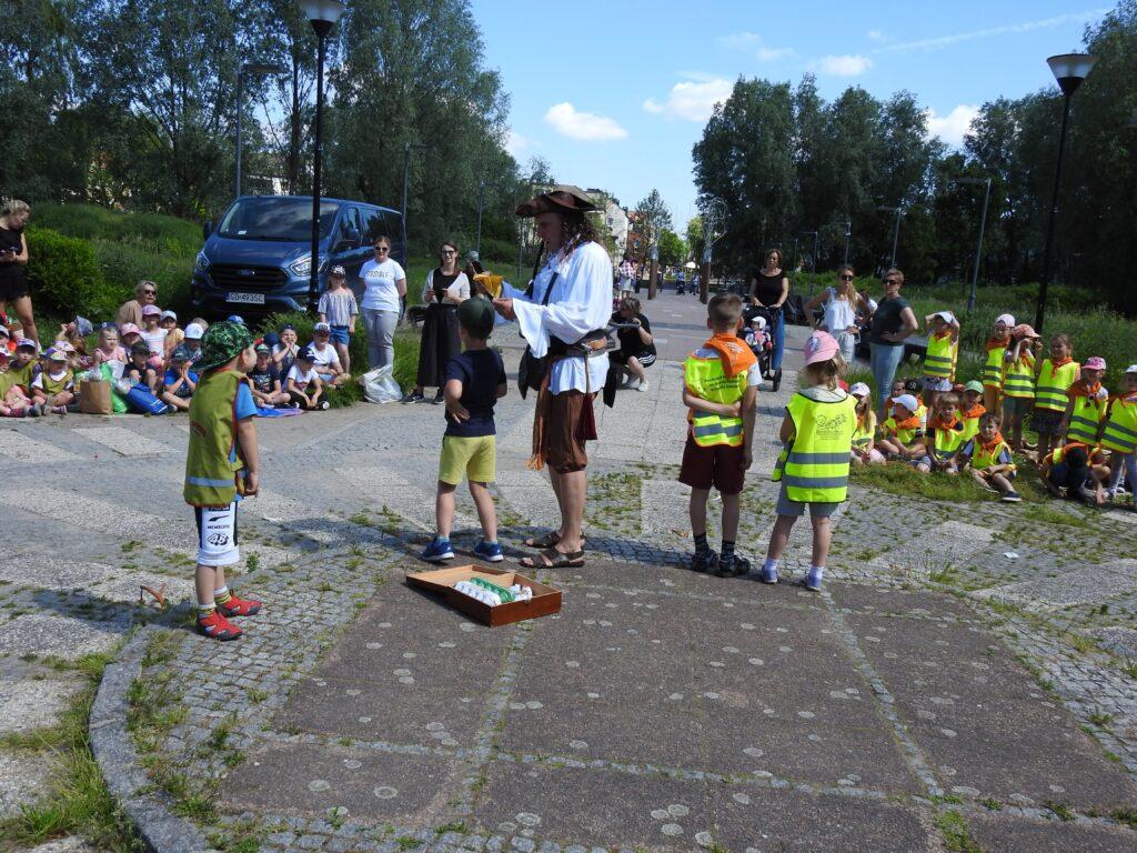 Mężczyzna w stroju pirata oraz czwórka dzieci zwrócona w stronę innej, dużej grupy dzieic. Zdjęcie na świeżym powietrzu