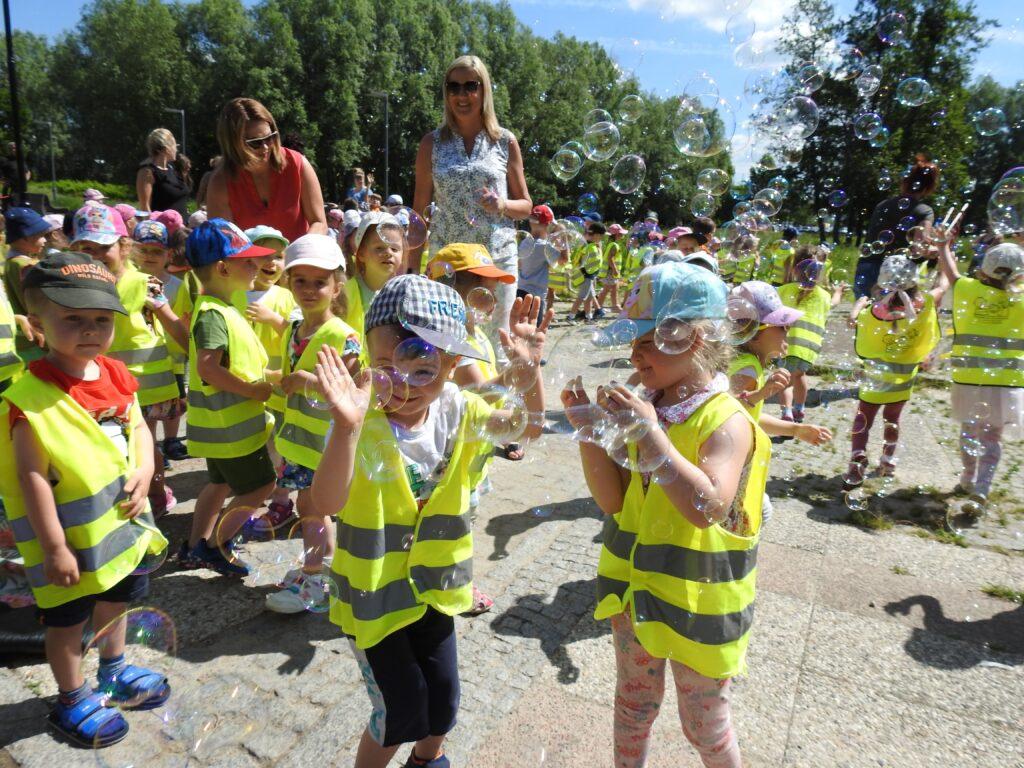 Duża grupa dzieci biega za bankami mydlanymi, które unoszą się nad ich głowami.