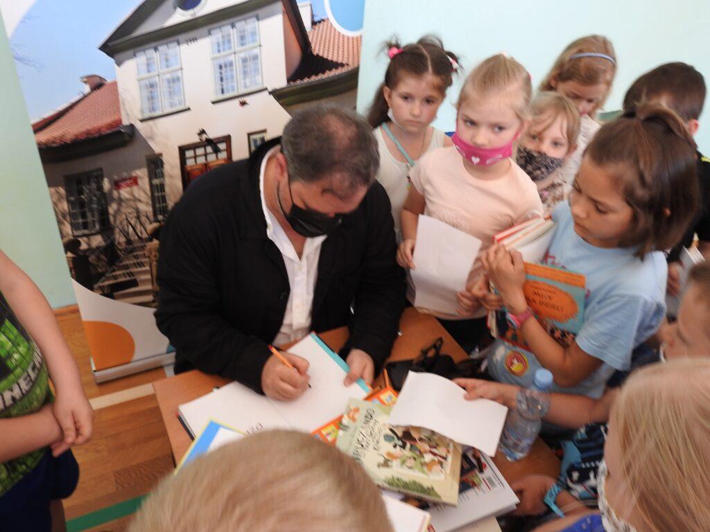Mężczyzna pisze w książce, wokół niego dzieci.