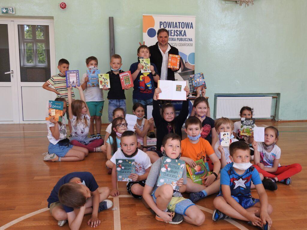 Mężczyzna i grupka dzieci z książkami pozują do zdjęcia.