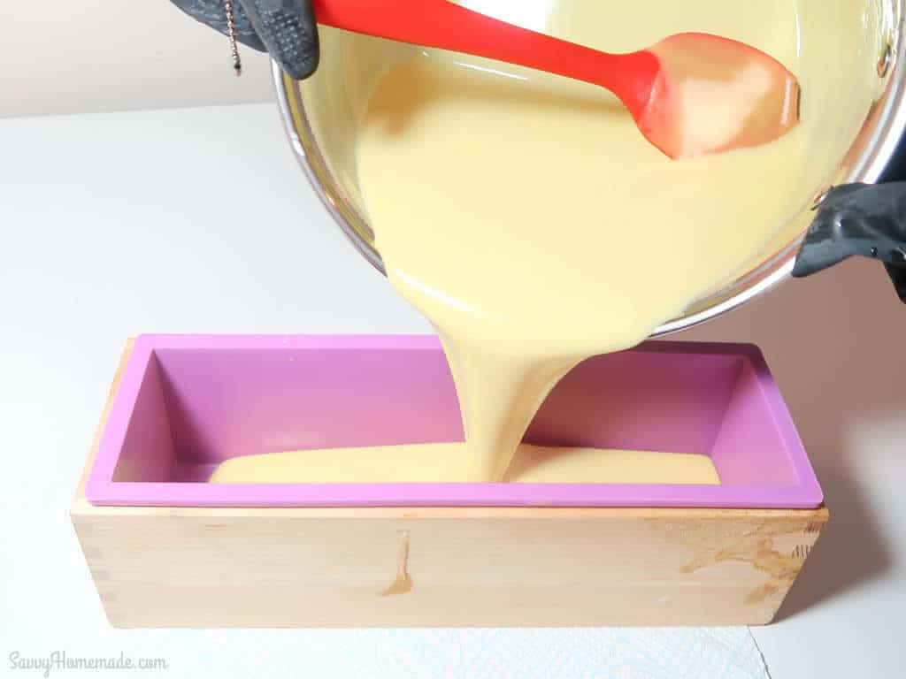 Working in layers, pour your soap batter, you'll want to do a layer of white soap about half way up.