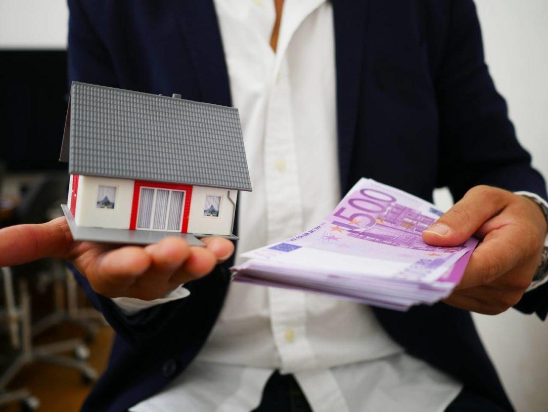 Mężczyzna trzyma w dłoniach pieniądze oraz dom