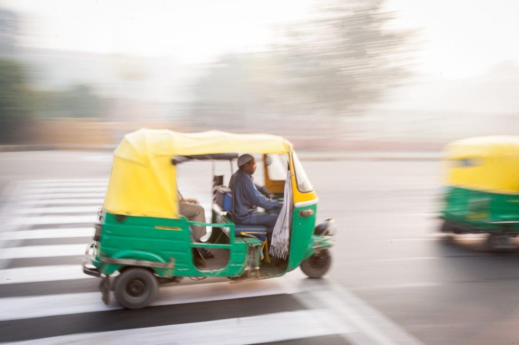 Tuk tuk speeding down the street in Delhi, India