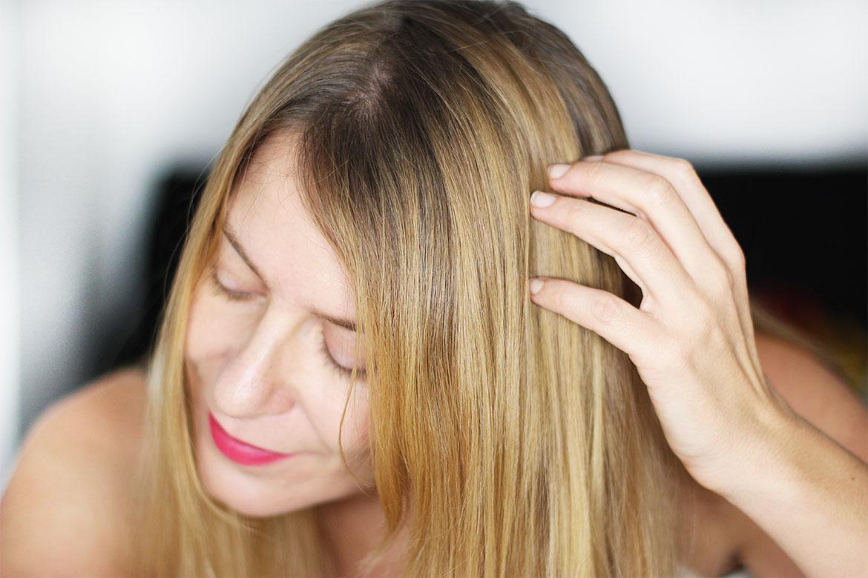 Femme blonde passant sa main dans ses cheveux