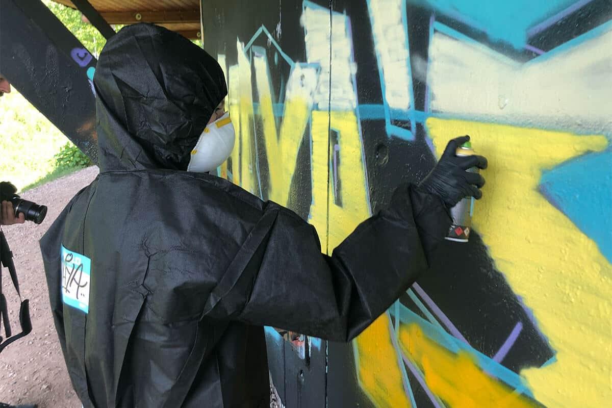 Um den Graffiti Kindergeburtstag von Maya gebührend zu feiern, haben wir von Graffiti Stuttgart mit ihren Gästen ein cooles Graffiti an der Außenwand vom Camp Feuerbach gemalt. Am Tag der Malaktion grundierte Micha die zu besprühende Fläche mit Wandfarbe, um dann die zuvor verabredeten Motive auf der Betonmauer vor zu skizzieren. Anschließend malte Maya mit ihren Freunden den Graffiti Style mit allen Buchstaben und Elementen farbig aus. Danach sprühte Micha noch die Konturen Outlines und die Lichteffekte.