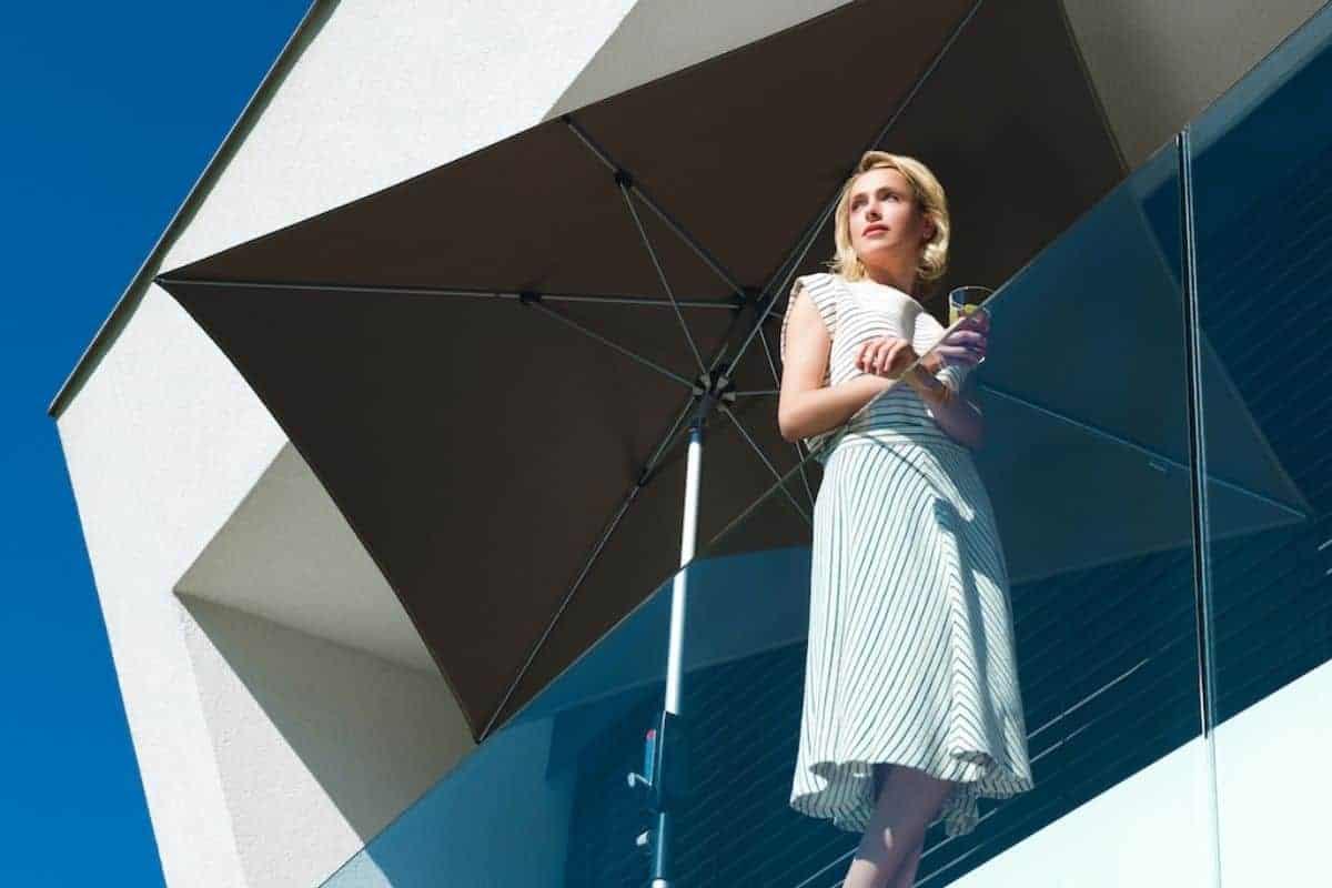 Frau unter Sonnenschirm auf Balkon