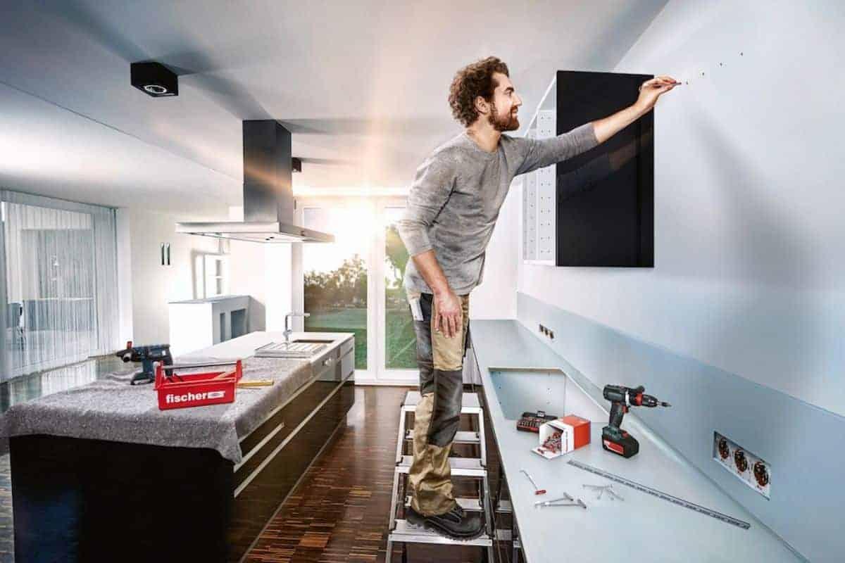 Mann auf Leiter steckt Dübel in Wand
