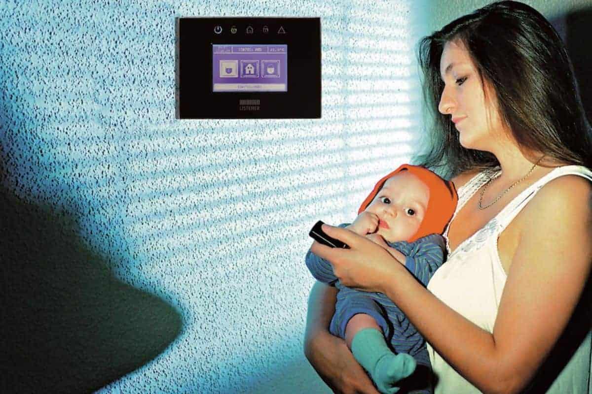 Frau mit Kleinkind an der Alarmanlage