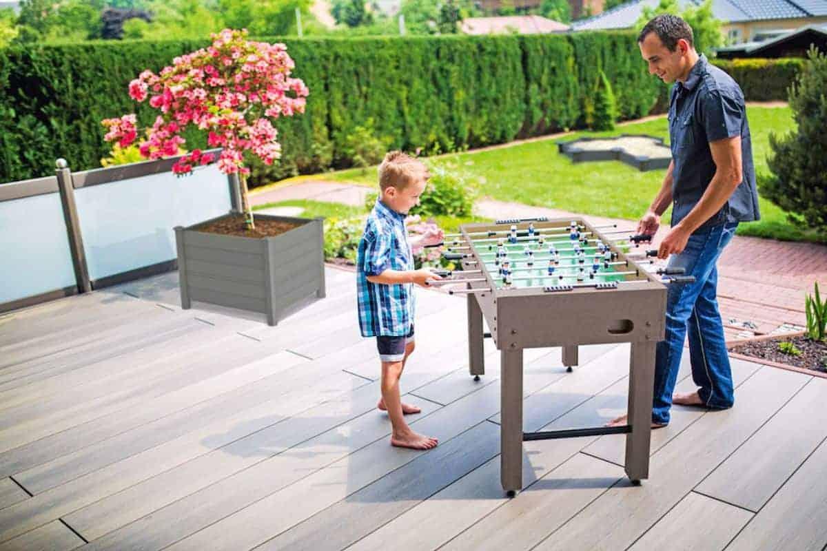 Vater spielt mit Sohn Kicker auf Terrasse