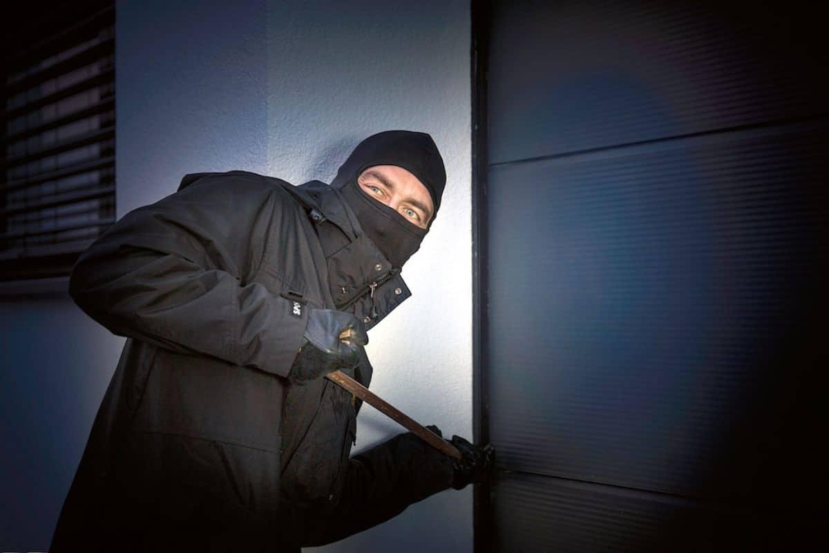 Einbrecher an der Tür mit Brechstange