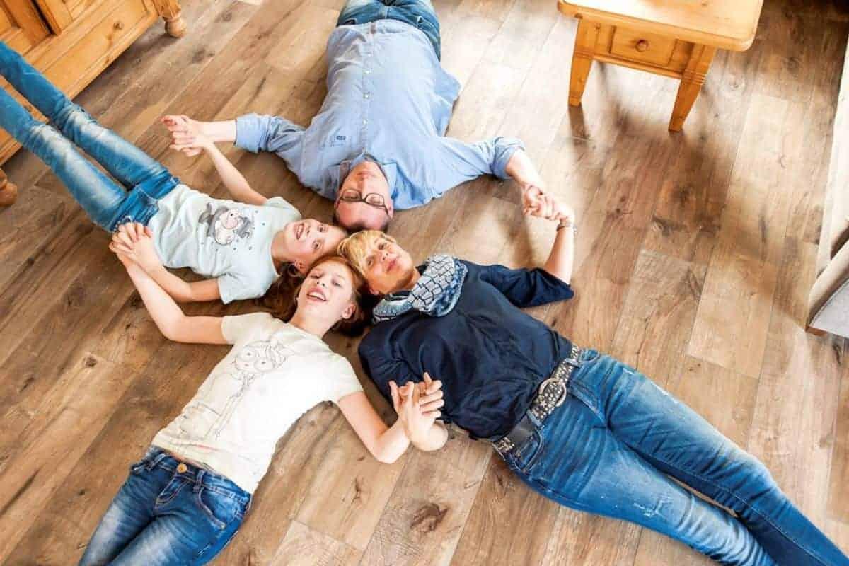 Familie liegt auf Keramik-Klimaboden