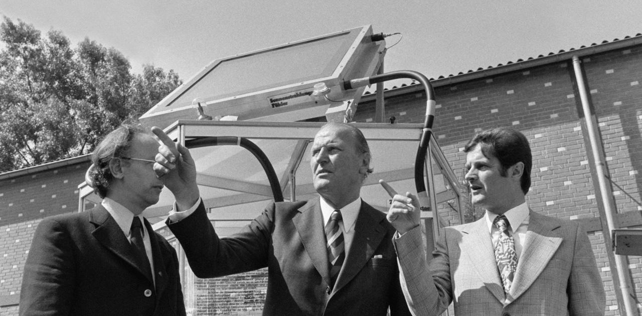 """Unter dem Motto """"Mehr denken - den Energieverbrauch senken"""" eröffnet am 7. Juni 1975 Bundesrat Willi Ritschard im Verkehrsmuseum Luzern die Sonderschau """"Energie"""". Ritschard, Mitte, und Eric Zanetti, Leiter der Arbeitsgruppe der Ausstellung, rechts, vor einem Sonnenkollektor zur Warmwasser-Aufbereitung. (KEYSTONE/PHOTOPRESS-ARCHIV/Str)"""