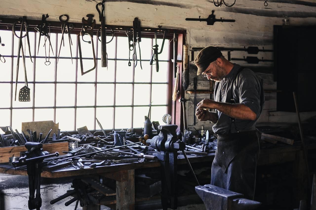 Robotnik stoi w warsztacie i przygląda się pracy swoich rąk