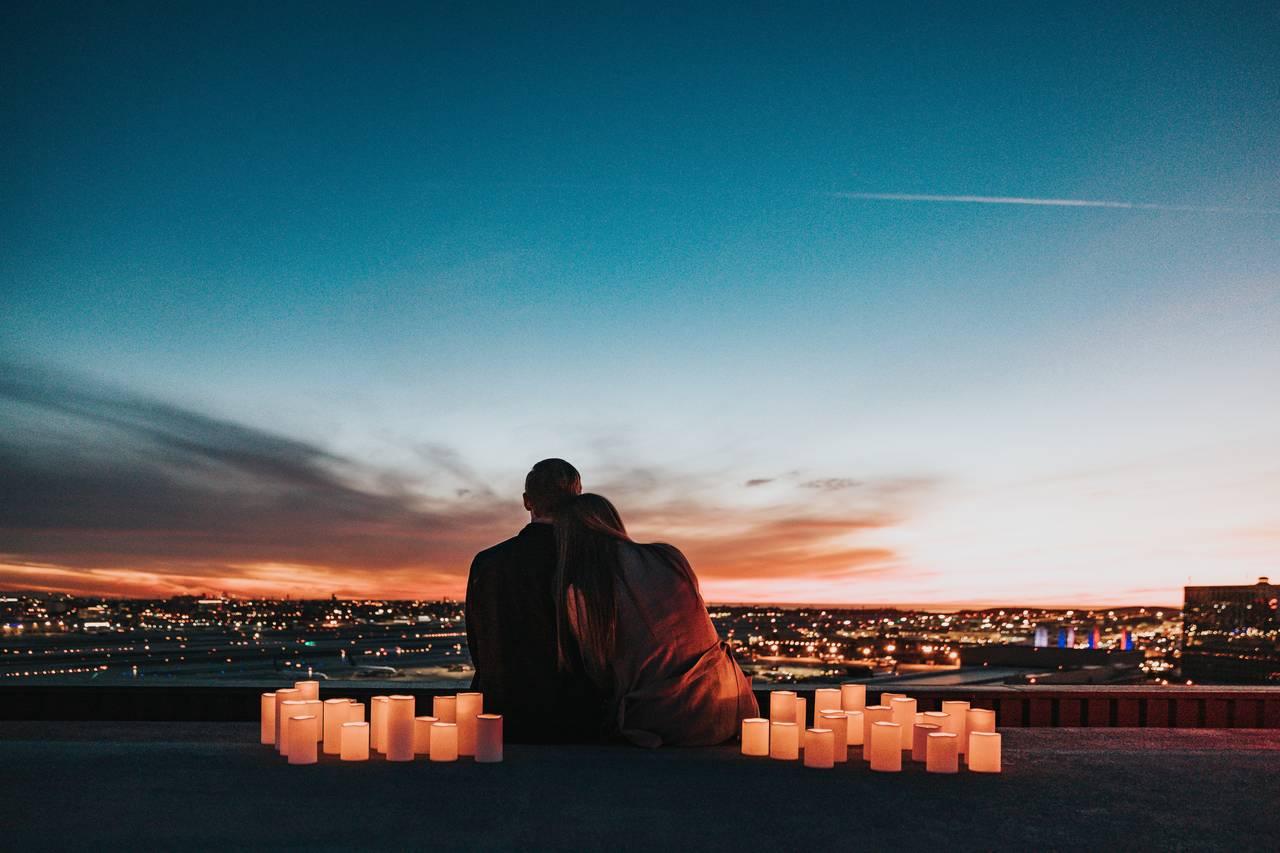 Młode małżeństwo siedzi n=w blasku świec na dachu budynku w trakcie swojej podróży poślubnej