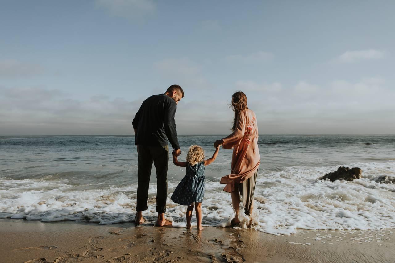 Rodzice razem z dzieckiem stoją na brzegiem morza