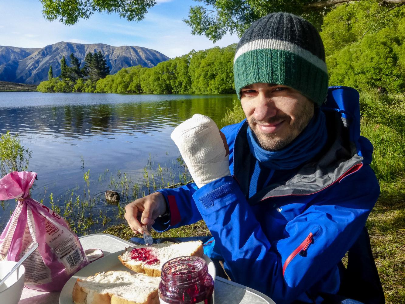 Jan Becker schmiert Marmelade auf ein Toastbroat an einem See
