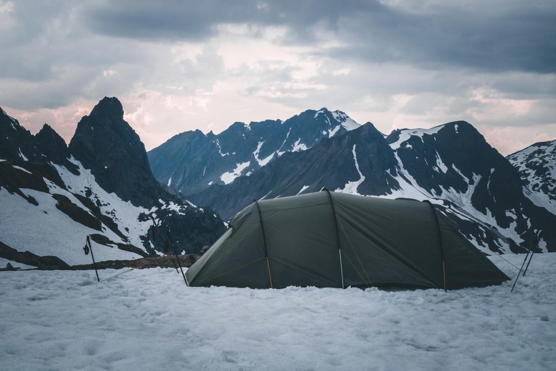 Zelt im Schnee mit Bergen im Hintergrund