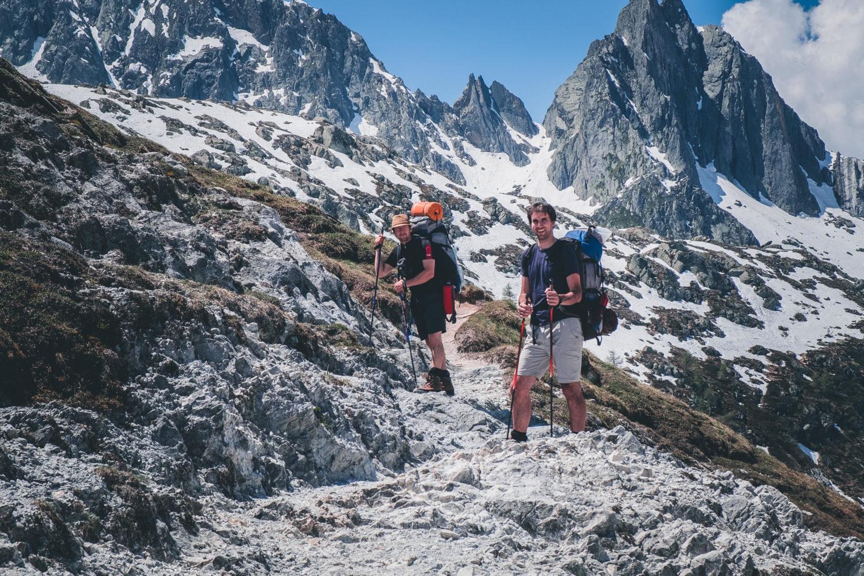 Zwei Wanderer vor hochalpiner Bergkulisse