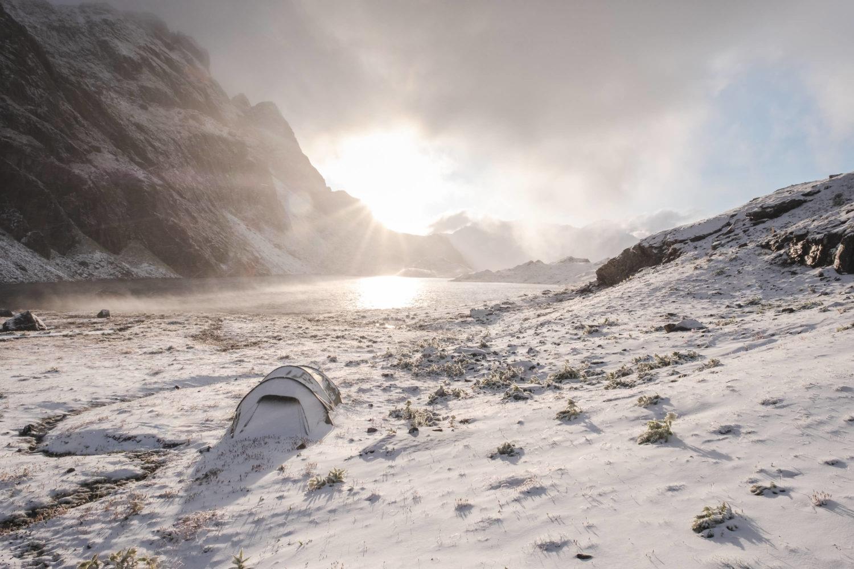 Eingeschneites Zelt mit Lunghinsee im Hintergrund beim Sonnenauf