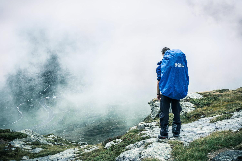 Wanderer mit Rucksack von Fjällraven vor wolkenverhangener Kuli