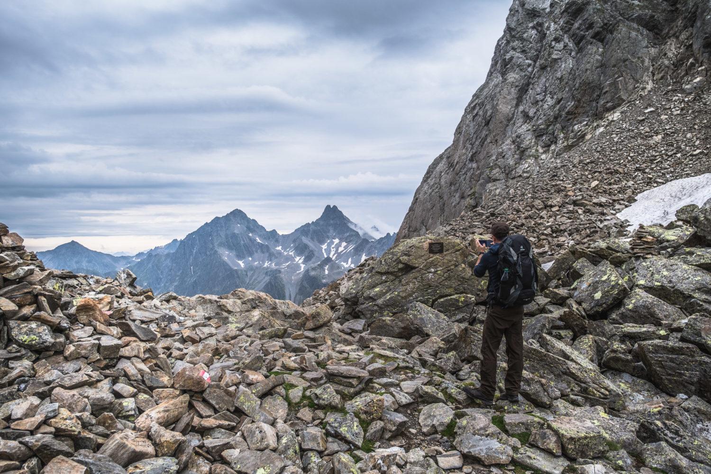Wanderer fotografiert mit dem Handy Berge gegenüber dem Kuchenjöchli