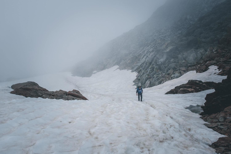 Wanderer geht durch Altschneefeld