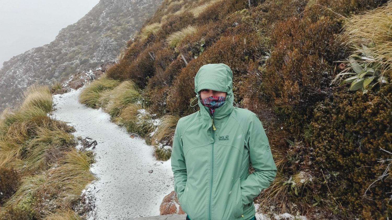 Wandererin steht im Schneeregen