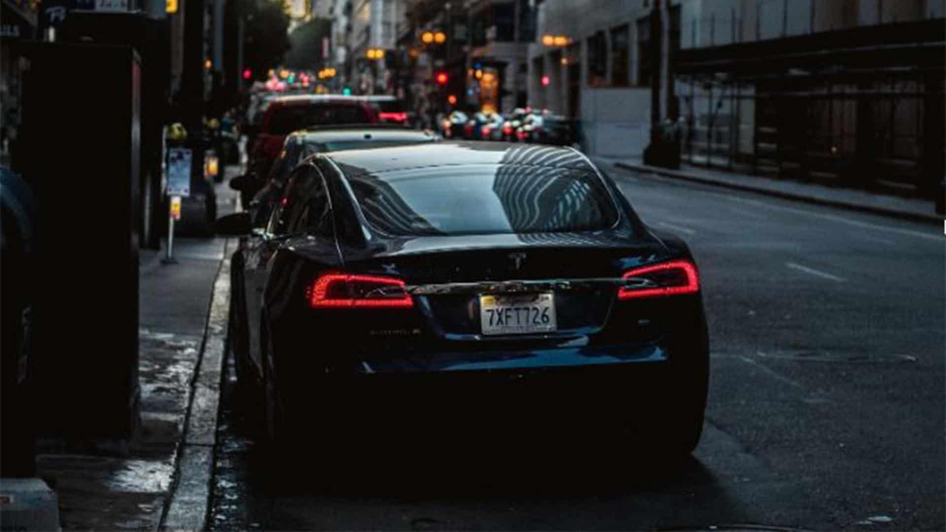 black tesla sitting on street for uber vs lyft pricing post