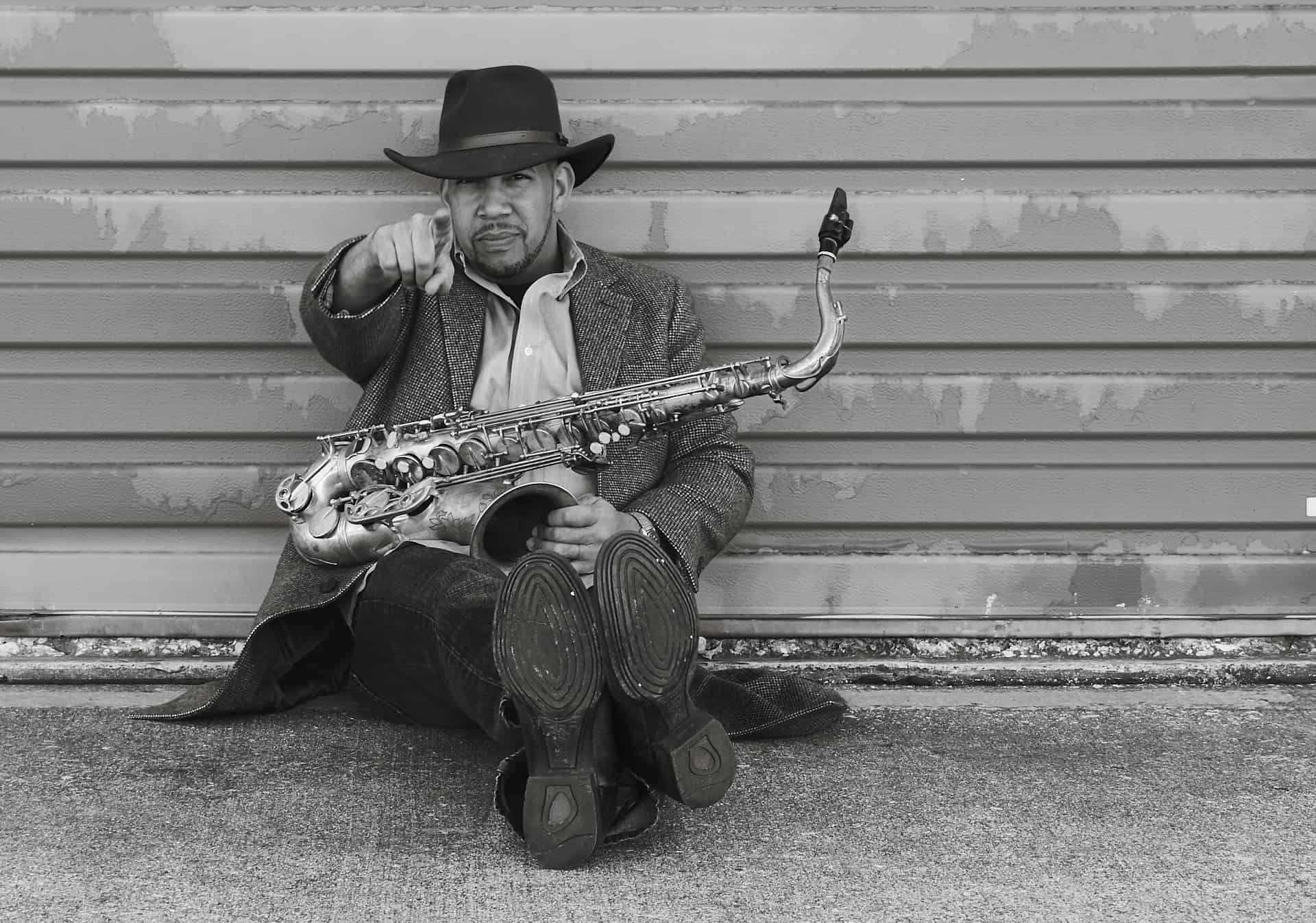 Saxophone player sitting on ground