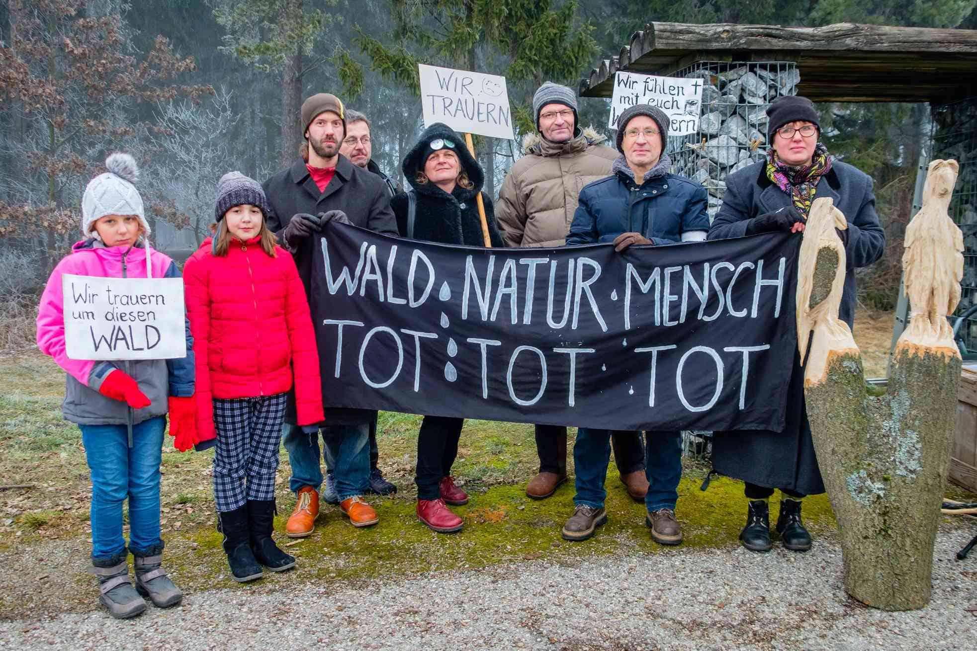 AktivistInnen halten Banner und Schilder hoch, mit denen sie auf das Waldsterben hinweisen und um den Wald trauern