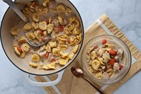 creamy chicken tortellini soup in a dutch oven on yellow placemat on marble background