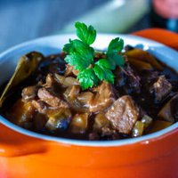 Bowl of Slow Cooker Beef and Ale Stew with beer bottle