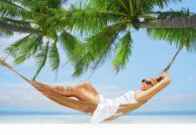 Kobieta leżąca na hamaku pod palmą