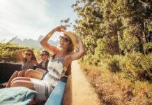 radosna dziewczyna w kapeluszu jedzie z przyjaciółmi na pace pickupa