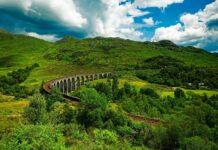 pociąg jadący przez wiadukt glenfinnan w szkocji
