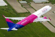 samolot Wizz Air lecący nad polami